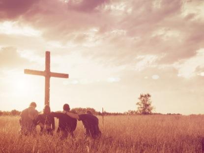 GROUP PRAYER KNEELING CROSS FIELD