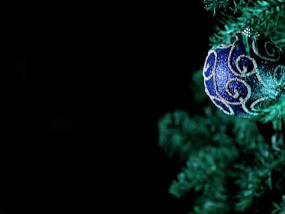 BLUE ORNAMENT HANGING ON A CHRISTMAS TREE WTIH BLACK BACKGROUND