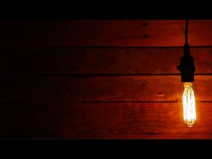LONG SWINGING VINTAGE LIGHTBULB ON URBAN BACKGROUND