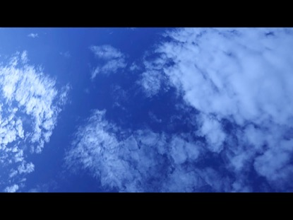 LOOKING DOWN ON ABSTRACT CLOUDS ON SUNNY BLUE SKY DAY