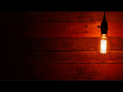 ROUND SWINGING VINTAGE LIGHTBULB ON URBAN BACKGROUND