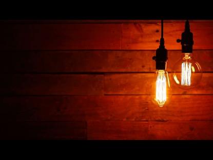 TWO SWINGING VINTAGE LIGHTBULB ON URBAN BACKGROUND