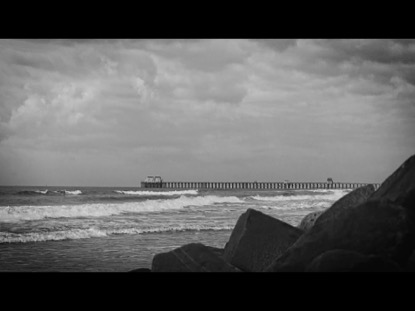 BLACK AND WHITE OCEANSIDE PIER WITH ROCKS