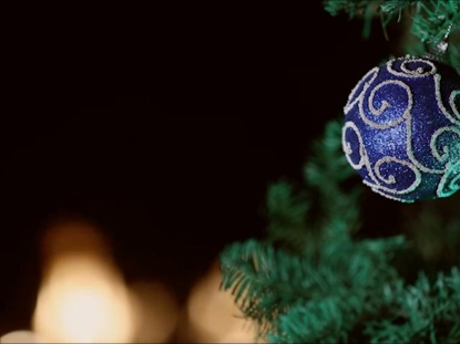 BLUE ORNAMENT HANGING ON A CHRISTMAS TREE WTIH FIRE