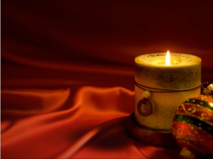 CHRISTMAS CANDLE ON SILK RED BACKGROUND WITH ORNAMENTS