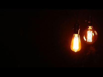 TWO SWINGING VINTAGE LIGHTBULB ON BLACK BACKGROUND